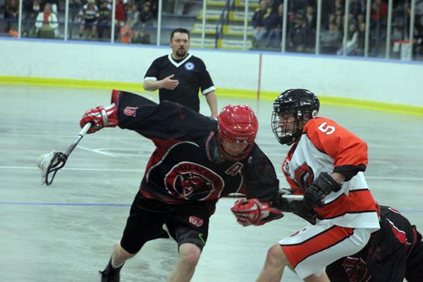 A Wallaceburg Red Devils player battles a Point Edward opponent in Sunday's opener - Photo by Jocelyn McLaughlin/ CKSN